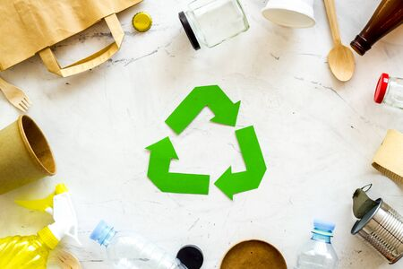 Ecology concept. Green recycling sign with waste materials, paper bag and cup, plastic bottles, flatware on white background top view