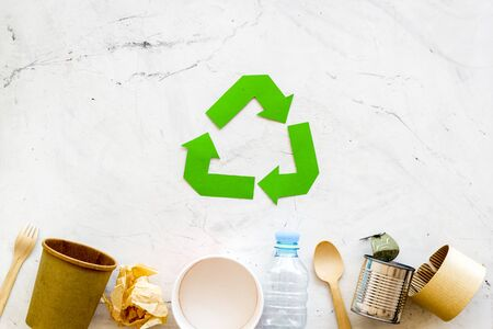 Green recycling symbol and different garbage, paper cup, plastic bottle, flatware, can for ecology on marble background top view