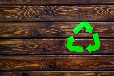 Garbage disposal. Green recycling sign for eco concept on wooden background top view mock up