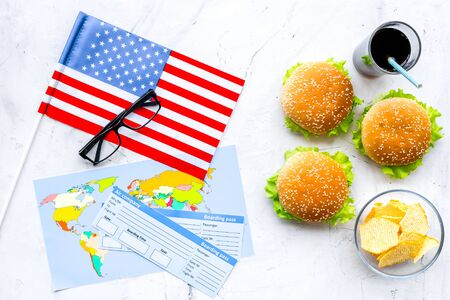 Traditional food. Burger, chips, map, tickets and USA flag for gastronomical tourism to America on marble background top view Banque d'images - 125648465