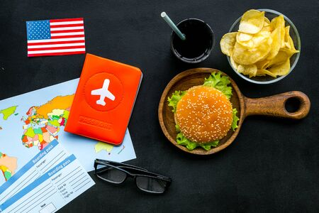 Burger, map, tickets, passport and USA flag for gastronomical tourism to America on black background top view Banque d'images - 125652331