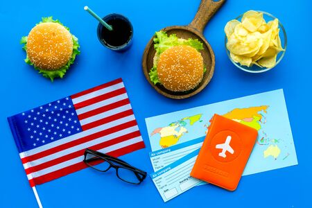 Traditional food. Burger, chips, map, passport, tickets and USA flag for gastronomical tourism to America on blue background top view Reklamní fotografie