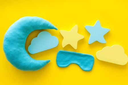 Go to bed. Sleep time concept with moon, stars, clouds toy, blindfolder on yellow background top view 版權商用圖片