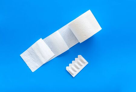 Disease of colon. Toilet paper roll and rectal suppository for proctology diseases concept on blue background top view