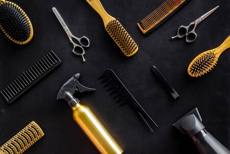 Combs, scissors and hairdresser tools in beauty salon work desk on black background top view pattern