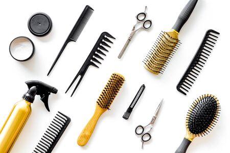 Peines, tijeras y herramientas de peluquería en la mesa de trabajo del salón de belleza en el patrón de vista superior de fondo blanco Foto de archivo