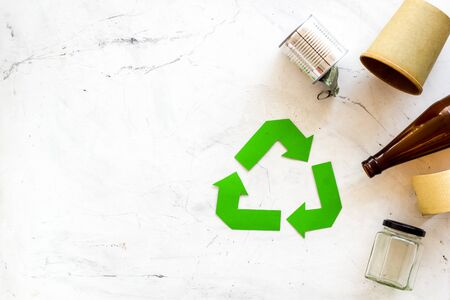Green recycling symbol and different garbage, plastic bottle, paper cup, can for ecology on white background top view mockup Stock Photo
