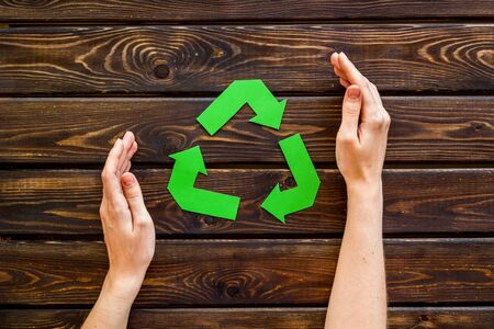 Green recycling symbol in hands for ecology on wooden background top view