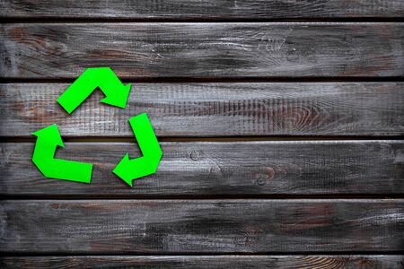 Green recycling symbol for ecology on wooden background top view copyspace