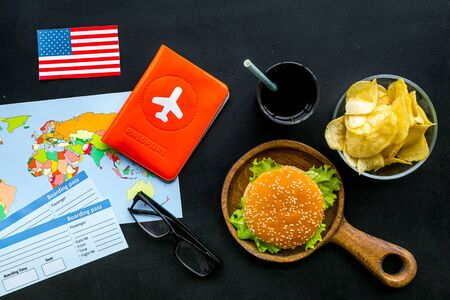 Gastronomical tourism concept with American flag, passport, tickets, map, glasses and food symbols, burgers, chips, drink on black background top view 版權商用圖片