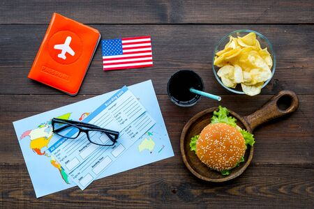 Gastronomical tourism concept with American flag, passport, tickets, map and food symbols, burgers, chips, drink on wooden background top view Banque d'images - 125729661