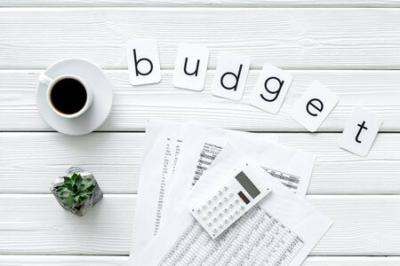 Business budget. Budget plan with calculator, coffee and plant on white wooden background top view Stockfoto