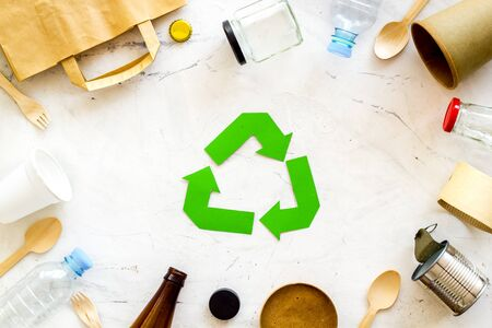 Green recycling symbol and different garbage, paper bag, cup, flatware, plastic bottle for ecology on marble background top view