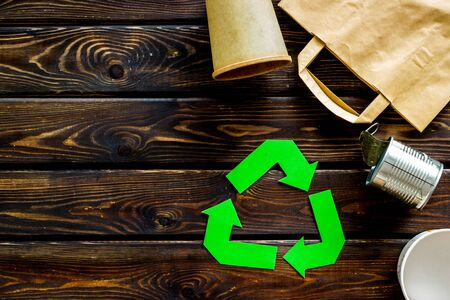 Green recycling symbol with paper bag, cup, can for ecology on wooden background top view copyspace