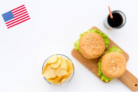 Independence Day of America celebration. Flag USA and national food, burgers, chips on white background top view
