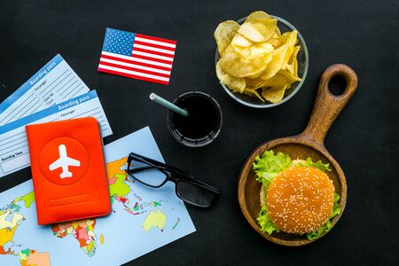 Traditional food. Burger, map, tickets, passport and USA flag for gastronomical tourism to America on black background top view Reklamní fotografie