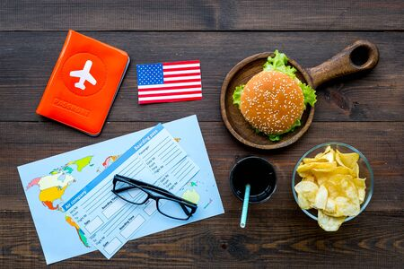 travel for traditional USA cuisine with burgers, drink, chips, passport, flight tickets, American flag and map on wooden background top view