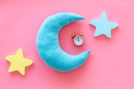 Insomnia concept. Night sleep concept with moon, stars toys and alarm clock on pink background top view