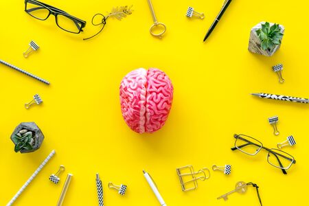 Brainstorm concept with brain, glasses, pens, keys, paperclip frame on yellow office desk background top view