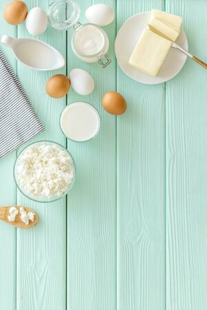 Dairy products. Eggs, butter, milk, yogurt, cottage for natural farm products yogurt on mint green wooden background top view copyspace 写真素材