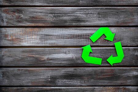 Garbage disposal. Green recycling sign for eco concept on wooden background top view mock-up 版權商用圖片