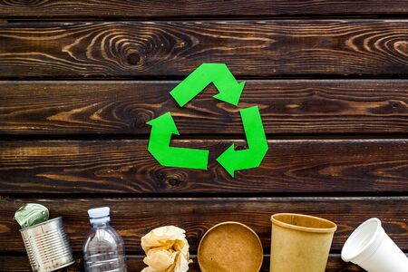 Green recycling symbol with paper cup, plastic bottle, can for ecology on wooden background top view 版權商用圖片