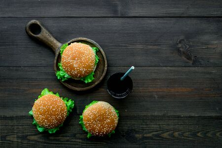 Traditional USA cuisine. National American food concept with burgers on pan and drink on wooden background top view