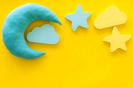 Dreams. Sleep time concept with moon, stars, cloud on yellow background top view
