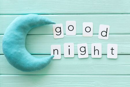 Go to bed. Good night text and moon for sleep concept on mint green wooden background top view