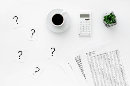 Business and accountant concept with coffee, budget, question mark and calculator on white office work desk background top view 版權商用圖片