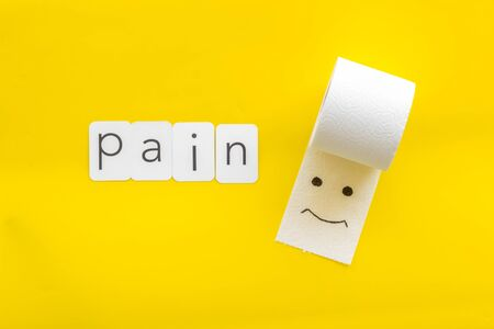Disease of colon. Proctology concept with pain text, toilet paper roll and painted face on yellow background top view Stock Photo