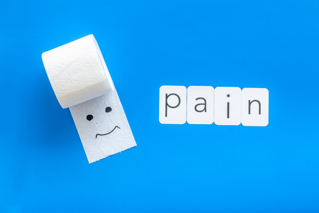 Disease of colon. Proctology concept with pain text, toilet paper roll and painted face on blue background top view Stock Photo