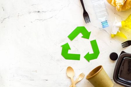 Eco friendly. green recycling sign with waste materials, plastic container and spoon, fork, paper cup for ecology save concept on marble background top view mock up 版權商用圖片