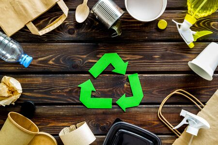 Ecology concept. Green recycling sign with waste materials, paper bag and cup, plastic bottles, flatware on wooden background top view