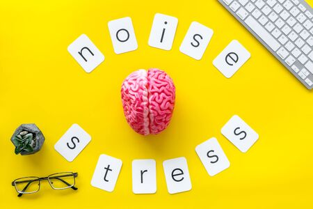 noise and stress copy, brain, keyboard, glasses on yellow office desk background top view Stock Photo