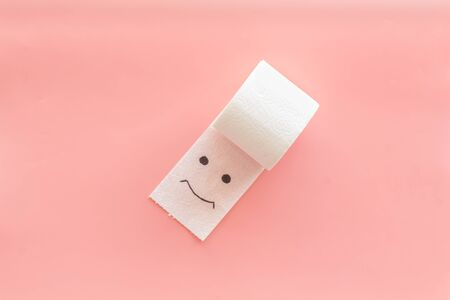 Toilet paper roll with painted face for proctology diseases concept on pink background top view