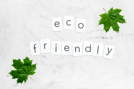 green maple leaves and eco friendly text for ecology concept on marble background top view