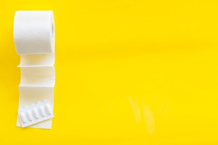 Proctology concept with toilet paper roll and rectal suppository on yellow background top view space for text