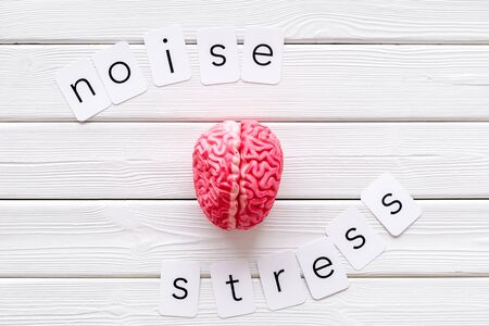 Business and mental health. Noise and stress copy, brain on white wooden office desk background top view Stock Photo