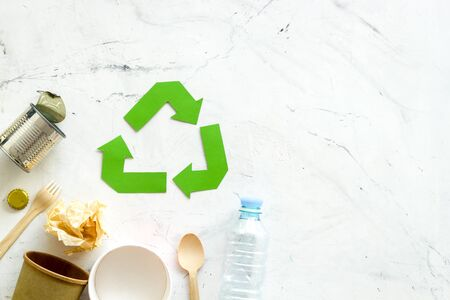Recycling sign with waste materials, bottle, cups, can for ecology concept on marble background top view copyspace