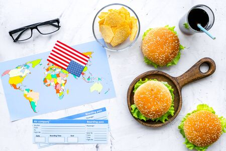 Travel for traditional USA cuisine with burgers, drink, chips, tickets, flag and map white background top view Banque d'images - 126189769