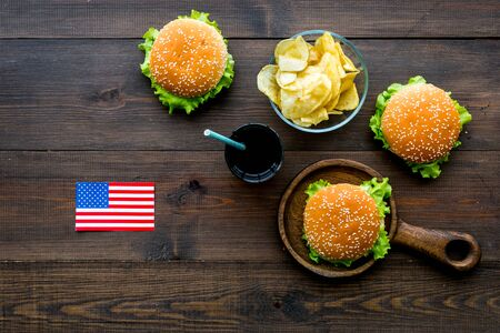 Independence Day of America concept with flag, burgers, chips and drink on wooden background top view