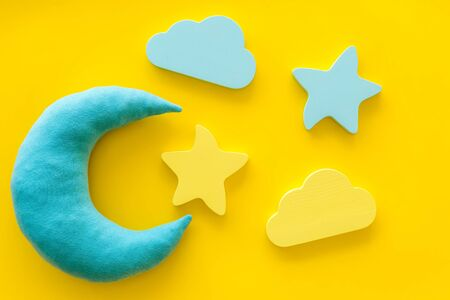 Sleep time concept with moon, stars, cloud on yellow background top view