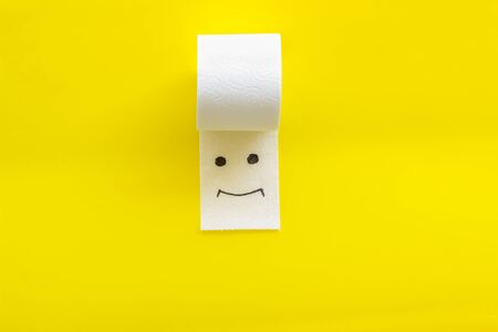 Disease of colon. Proctology concept with toilet paper roll and painted face on yellow background top view