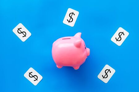 Business and budget concept with piggy bank and dollar sign on blue office background top view Stockfoto