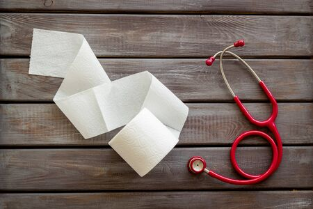 Proctology concept with toilet paper roll and stethoscope on wooden background top view