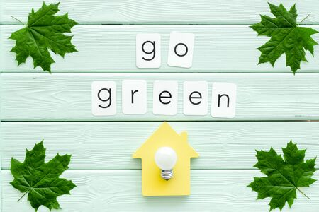 Go green copy with green maple leaves, house and lamp for ecology concept on mint green wooden background top view Foto de archivo - 126189820