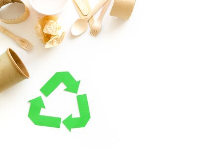 Green recycling symbol and different garbage, cup, flatware for ecology on white background top view mock up