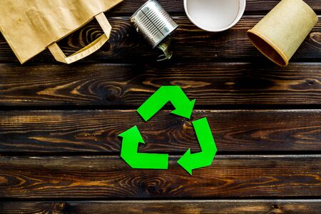 Green recycling symbol with paper bag, cup, can for ecology on wooden background top view 版權商用圖片