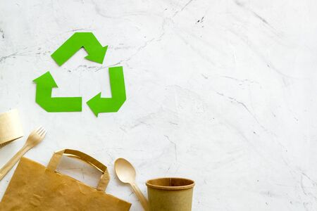 Eco friendly. Green recycling sign with waste materials, cups, tableware, paper bag for ecology save concept on marble background top view copyspace